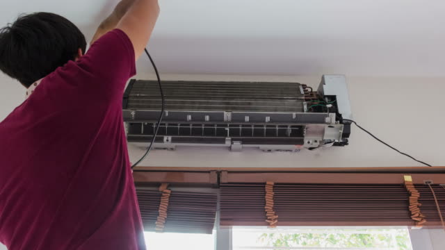 4K-Time lapse; man clean air conditioner in room